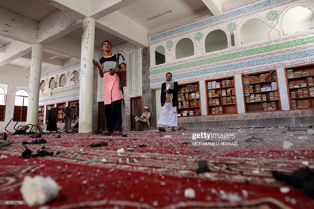 Yemeni armed men inspect the damage following a bomb explosion at the Badr mosque in southern Sanaa on March 20 2015 Triple suicide bombings killed...