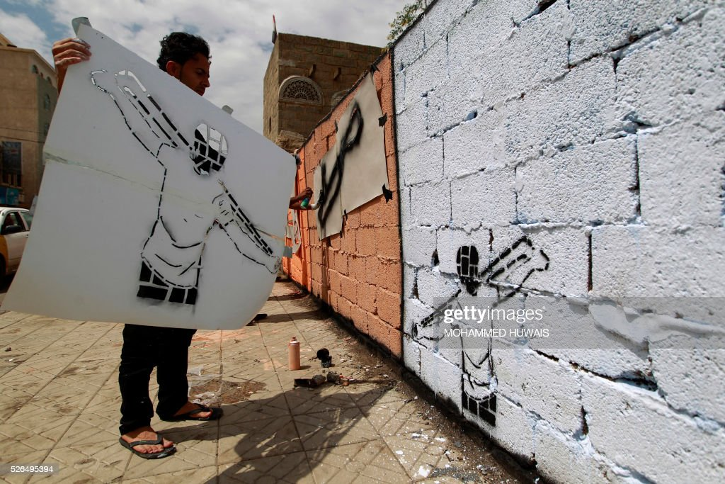 A Yemeni artist holds a paper-stencil after spraying it on a wall in the capital Sanaa in support of peace in the war-affected country, on April 30, 2016. / AFP / MOHAMMED