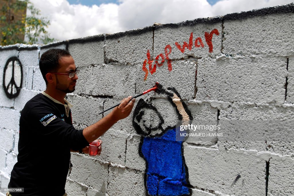 A Yemeni artist paints a graffiti on a wall in the capital Sanaa in support of peace in the war-affected country, on April 30, 2016. / AFP / MOHAMMED