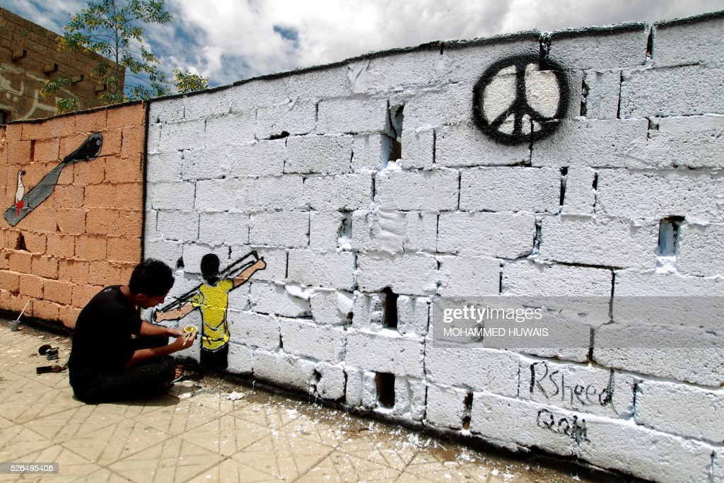 A Yemeni artist sprays graffiti on a wall in the capital Sanaa in support of peace in the war-affected country, on April 30, 2016. / AFP / MOHAMMED