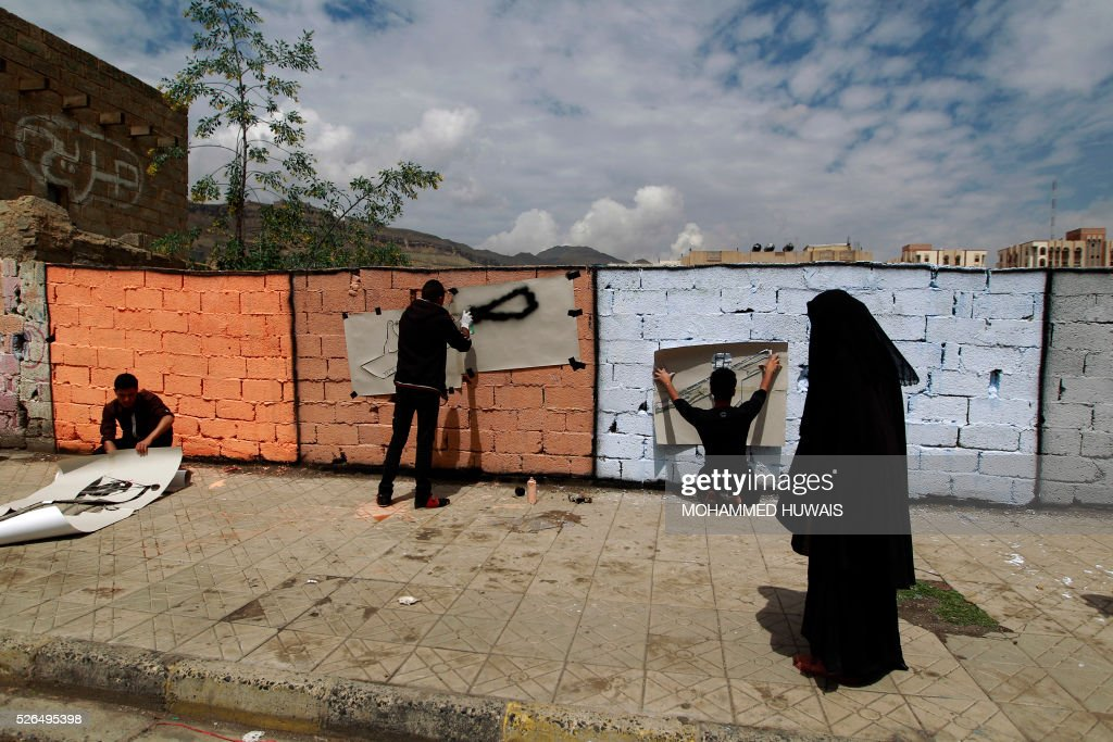 Yemeni artists spray graffiti on a wall in the capital Sanaa in support of peace in the war-affected country, on April 30, 2016. / AFP / MOHAMMED