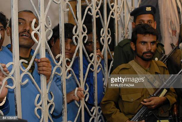 Yemeni Aziz Yahya alAbdi stands behind the bars as Yemeni security men guard the court room during his second court hearing on December 22 2008 in...