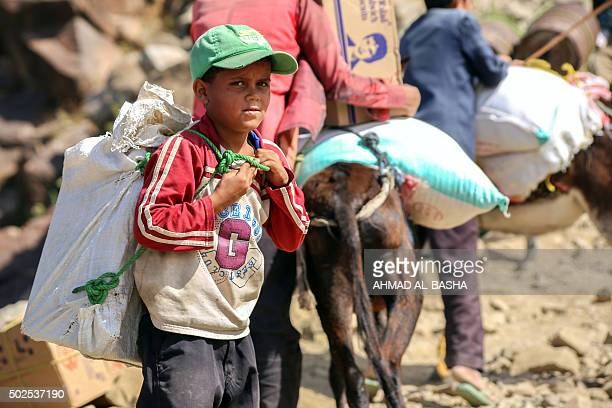 A Yemeni boy carries a bag of food as he walks through the mountains along the only path accessible between the southern cities of Aden and Taez on...
