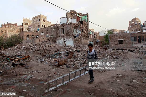 A Yemeni boy carries a ladder on March 23 2016 in front of buildings that were damaged by air strikes carried out by the Saudiled coalition over the...