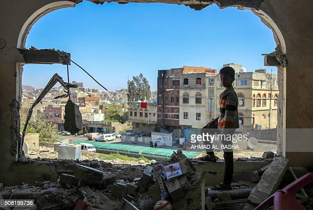 Yemeni boy checks the damage following a mortar shell attack on the country's flashpoint southern city of Taez on February 3 as clashes between...
