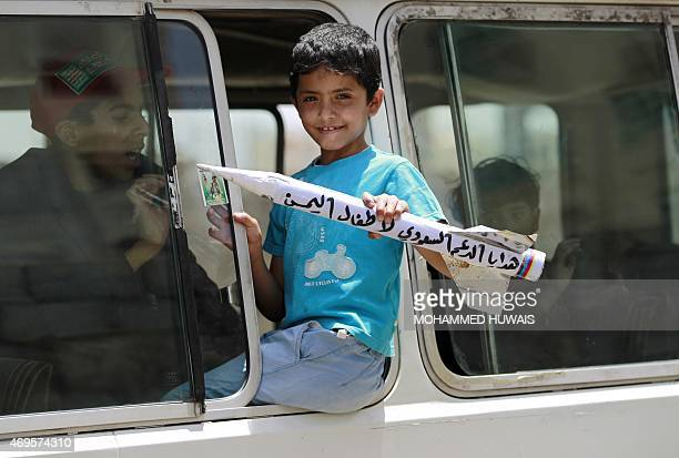 A Yemeni boy holds a fake rocket bearing writing reading in Arabic 'A gift from Saudi Arabia to the Yemeni children' and 'You will not weaken us...