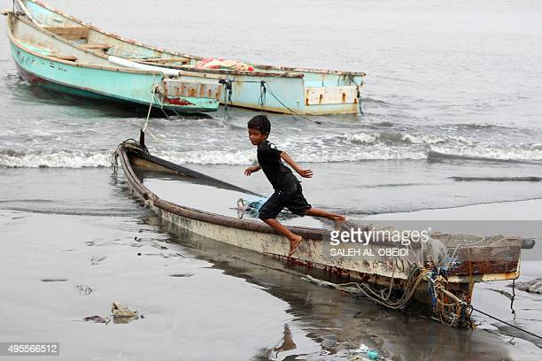 A Yemeni boy plays on a fishing boat beached in the southern port city of Aden on November 3 following a tropical cyclone that has slammed into the...