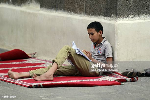 A Yemeni boy reads his textbook at a mosque in Sanaa's old city on September 3 2015 More than 13 million children are being denied an education by...