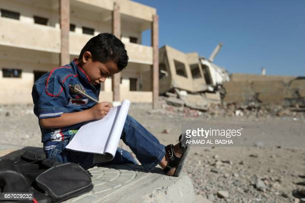 Yemeni boy school writes as he sits outside a school on March 16 that was damaged in an air strike in the southern Yemeni city of Taez The conflict...