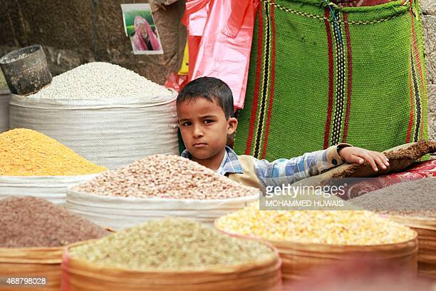 A Yemeni boy sits between bags of grain at a market in the old city of the capital Sanaa on April 7 2015 The Red Cross warned of a 'catastrophic'...