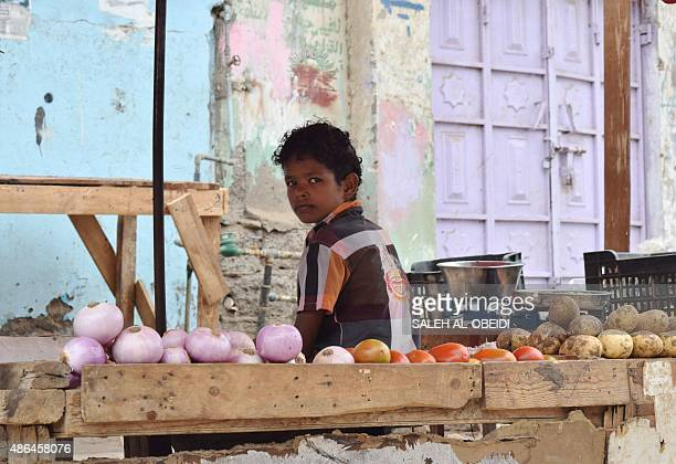 A Yemeni boy sits next to stalls at a market in the city of Aden on September 4 2015 More than 13 million children are being denied an education by...