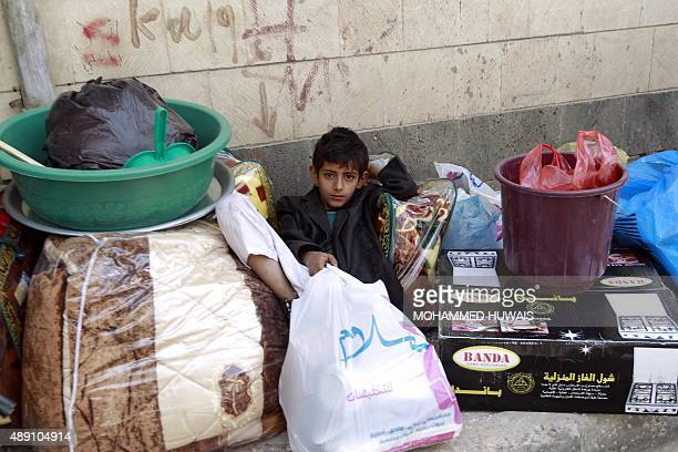 A Yemeni boy sits on the pavement next to his family belongings as they leave their home following air strikes carried out by the Saudiled coalition...