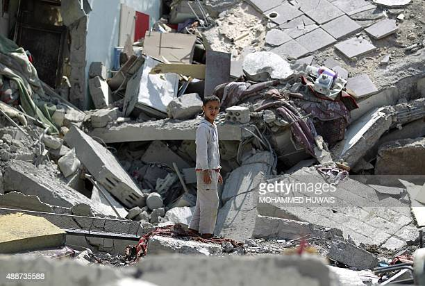 A Yemeni boy stands in the rubble of buildings on September 17 2015 which were destroyed by air strikes carried out by the Saudiled coalition in the...