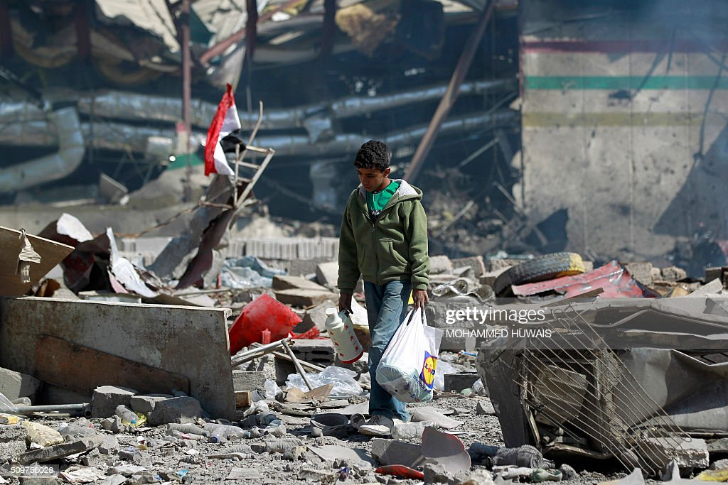 A Yemeni boy walks amid the ruins of a school and a bowling club hit by an air-strike carried out by the Saudi-led coalition, in the capital Sanaa, on February 12, 2016. / AFP / MOHAMMED HUWAIS