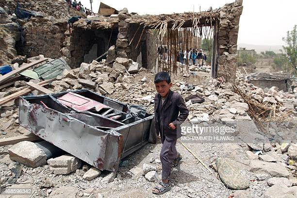 A Yemeni boy walks past the rubble of destroyed houses in the village of Bani Matar 70 kilometers West of Sanaa on April 4 a day after it was...