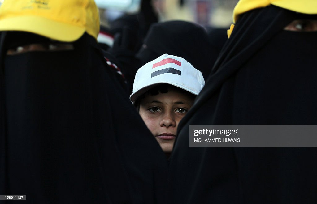 A Yemeni boy wearing a cap bearing the colours of his national flag is seen behind two women protestors, wearing the niqab, during a pro-democratic demonstration in Sanaa on January 3, 2013, demanding a quicker implementation of President Abdrabuh Mansur Hadi's latest orders to restructure Yemen's military. AFP PHOTO/ MOHAMMED HUWAIS