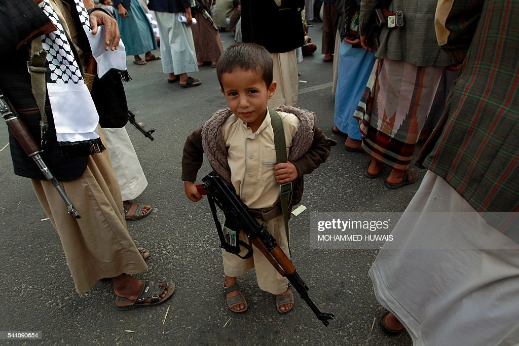 A Yemeni child carries a weapon during a rally gathering supporters of the Shiite Huthi movementto mark the Quds (Jerusalem) International day, in support of Palestinians on July 1, 2016 in the capital Sanaa. / AFP / MOHAMMED