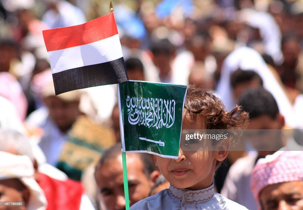 A Yemeni child holds Saudi and Yemeni national flags during a demonstration in the strategic city of Taez on March 27 in support of the Saudiled...