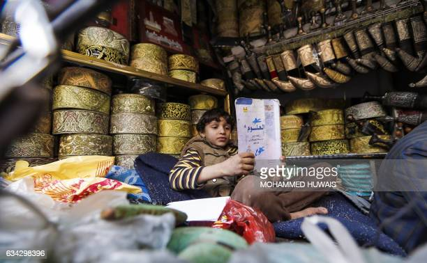 A Yemeni child reads a book in a shop selling 'janbiyas' traditionallyworn short curved daggers in Sanaa's Suq AlMelh on January 24 2017 The...