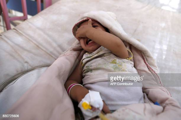 TOPSHOT A yemeni child who is suspected of being infected with cholera cries at a hospital in the capital Sanaa on August 12 2017 A cholera outbreak...