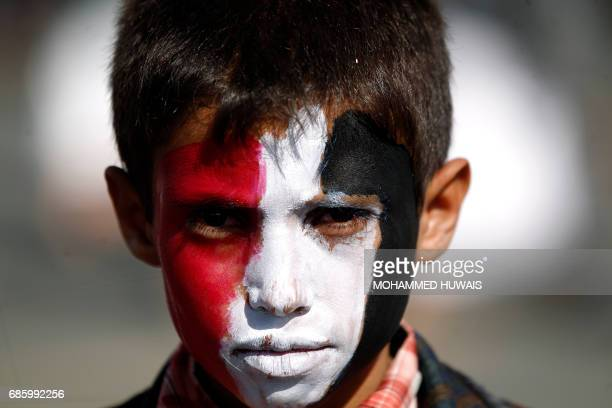 A Yemeni child with his face painted in the colours of his national flag looks on during an antiUS protest staged by supporters of the Huthi rebels...