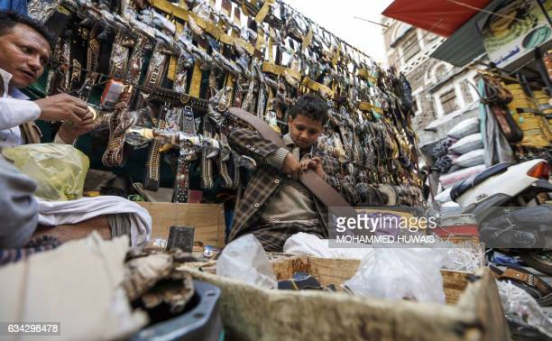 A Yemeni child works in a shop selling 'janbiyas' traditionallyworn short curved daggers in Sanaa's Suq AlMelh on January 24 2017 The devastating...