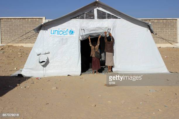 Yemeni children open the entrance of a tent that serves as a classroom at a school that was damaged in the country's ongoing conflict between the...