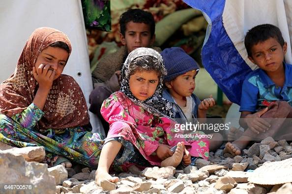 Yemeni children sit in front of a tent built on stone covered ground near the Mocha port on the Red Sea in Taiz Yemen on March 1 2017 Escalating...