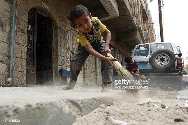 Yemeni children sweep the pavement littered with rubbish as garbage trucks hardly run due to an acute shortage of fuel in the capital Sanaa on May 4...