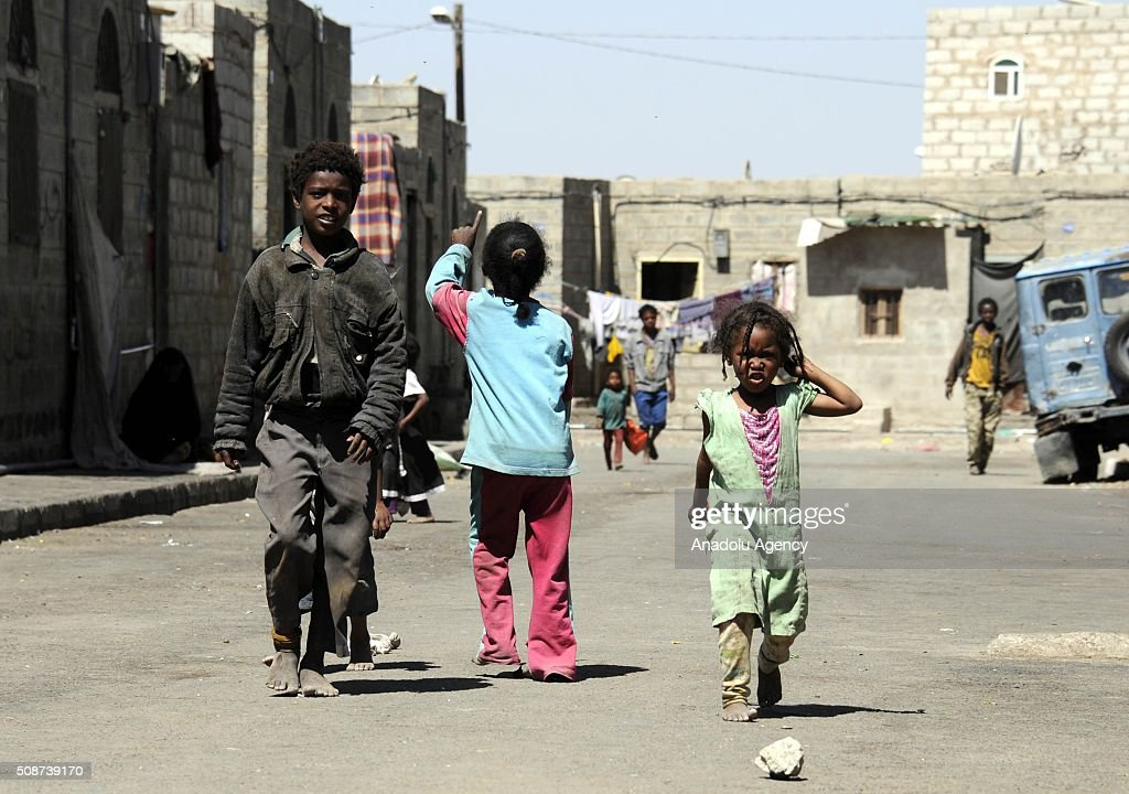 Yemeni children walk on a road barefoot in Savan neighborhood as Saudi-led airstrikes continue in Sana'a, Yemen on February 6, 2016.