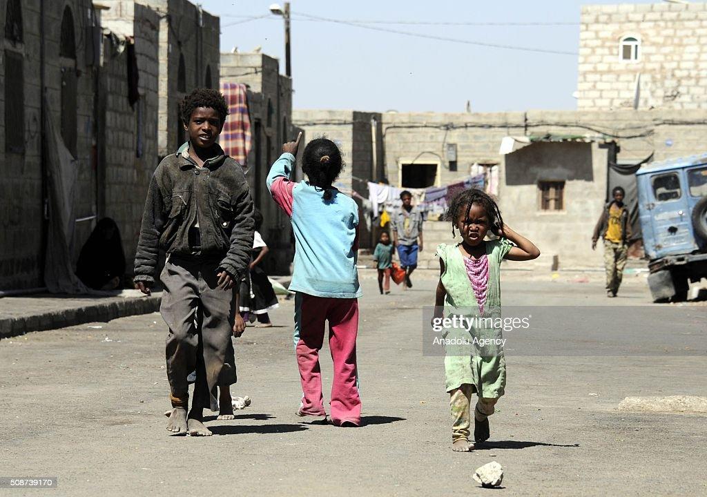 Yemeni children walk on a road barefoot in Savan neighborhood as Saudi-led airstrikes continue in Sana'a, Yemen on February 6, 2016.