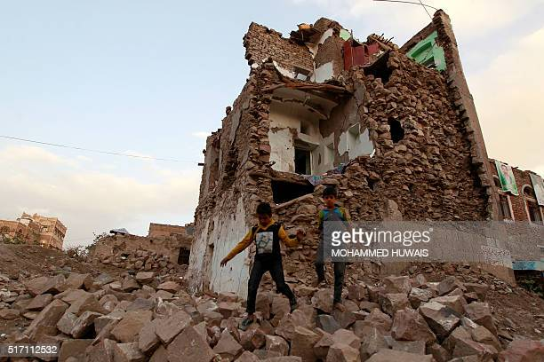 Yemeni children walk on March 23 2016 on stones in front of buildings that were damaged by air strikes carried out by the Saudiled coalition over the...