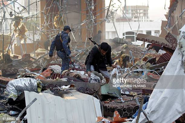 A Yemeni collects items amidst the rubble of a destroyed funeral hall building following reported airstrikes by Saudiled coalition airplanes on the...