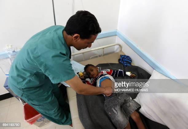 A Yemeni doctor checks a child suspected of being infected with cholera at a makeshift hospital in Sanaa on June 9 2017 Yemen is descending into...