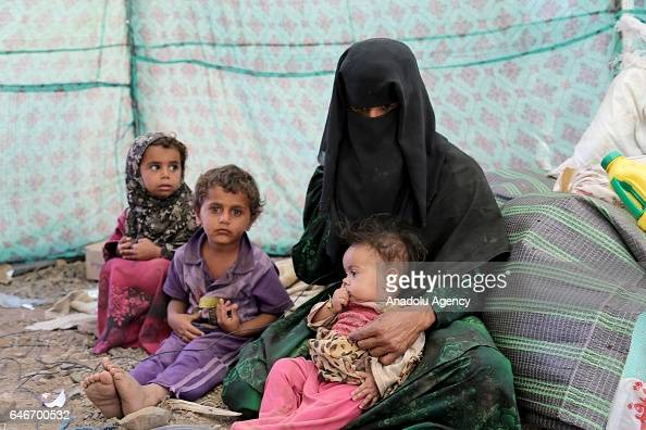Yemeni family sits on stone covered ground inside of a tent near the Mocha port on the Red Sea in Taiz Yemen on March 1 2017 Escalating clashes cause...