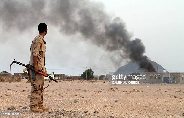 A Yemeni fighter from the Popular Resistance Committees looks towards smoke rising from a building after they reportedly attacks military vehicle...