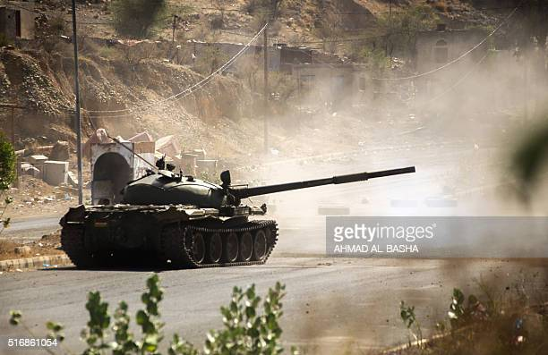 A Yemeni fighter loyal to Yemen's exiled President Abedrabbo Mansour Hadi fires from a tank during clashes with Shiite Huthi rebels west of the city...