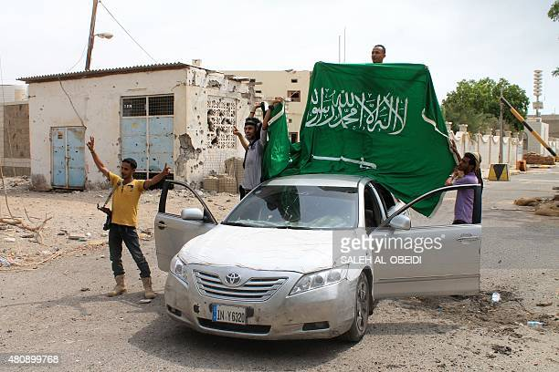 Yemeni fighters loyal to exiled President Abedrabbo Mansour Hadi deploy a Saudi national flag next to the Saudi consulate after they retook it from...