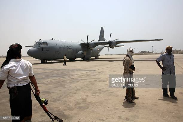 Yemeni fighters loyal to exiled President Abedrabbo Mansour Hadi stand on the tarmac as a Qatari plane carrying relief aid arrives at Aden's...
