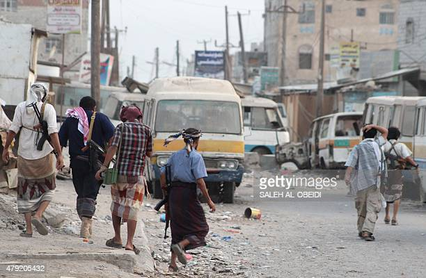Yemeni fighters loyal to exiled President Abedrabbo Mansour Hadi walk on a damaged street in the Dar Saad suburb of the southern city of Aden on July...
