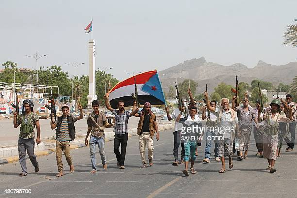 Yemeni fighters of the southern separatist movement loyal to exiled President Abedrabbo Mansour Hadi hold the movement's flag and brandish their...