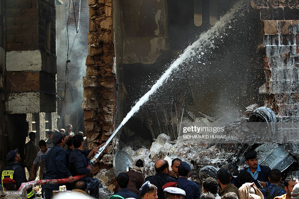Yemeni firefighters douse the site where a military aircraft crashed in a residential neighbourhood in Sanaa on February 19, 2013. A Yemeni military aircraft ploughed into a building in a residential neighbourhood of Sanaa killing at least nine people, medics and witnesses said. A military source was unable to say what caused the crash. AFP PHOTO/MOHAMMED HUWAIS