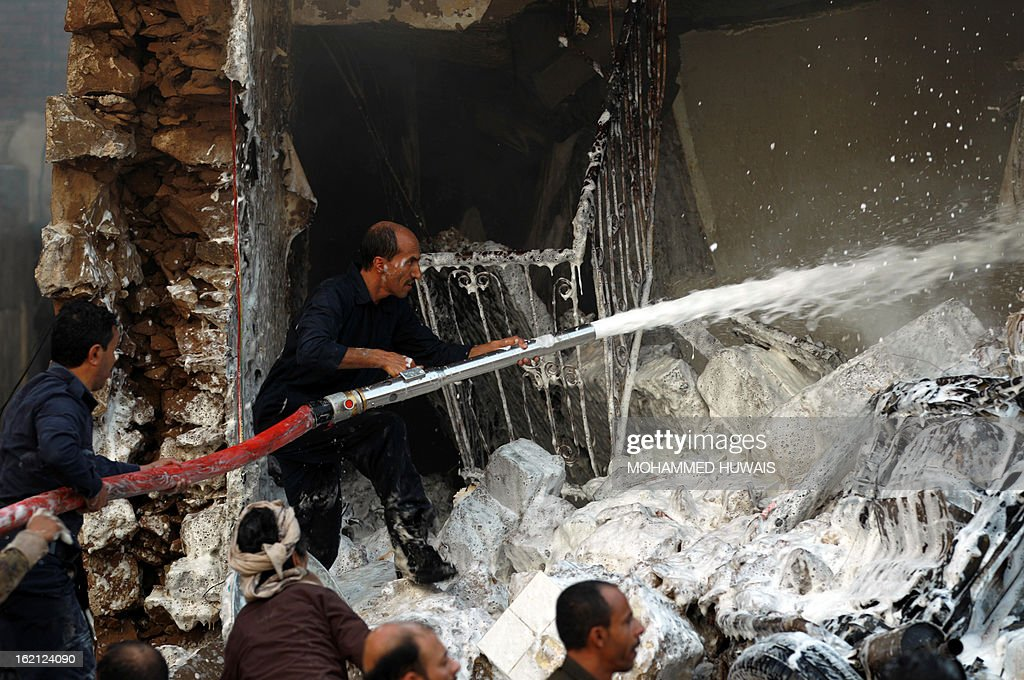 Yemeni firefighters douse the site where a military aircraft crashed in a residential neighbourhood in Sanaa on February 19, 2013. A Yemeni military aircraft ploughed into a building in a residential neighbourhood of Sanaa killing at least nine people, medics and witnesses said. A military source was unable to say what caused the crash.