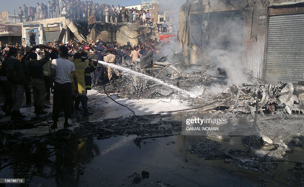 Yemeni firefighters extinguish a blaze at the scene of a military plane crash in Sanaa on November 21, 2012. Ten people including the pilot were killed as the Antonov jet tried to make an emergency landing when an engine failed, Yemen's defence ministry and an airport source said.