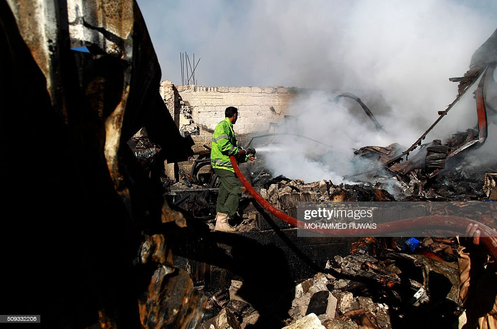 Yemeni firefighters extinguish a fire in buildings destroyed an air-strike by the Saudi-led coalition on February 10, 2016 in the capital Sanaa. The coalition has been carrying out air strikes against Iran-backed rebels across Yemen since March. / AFP / MOHAMMED HUWAIS