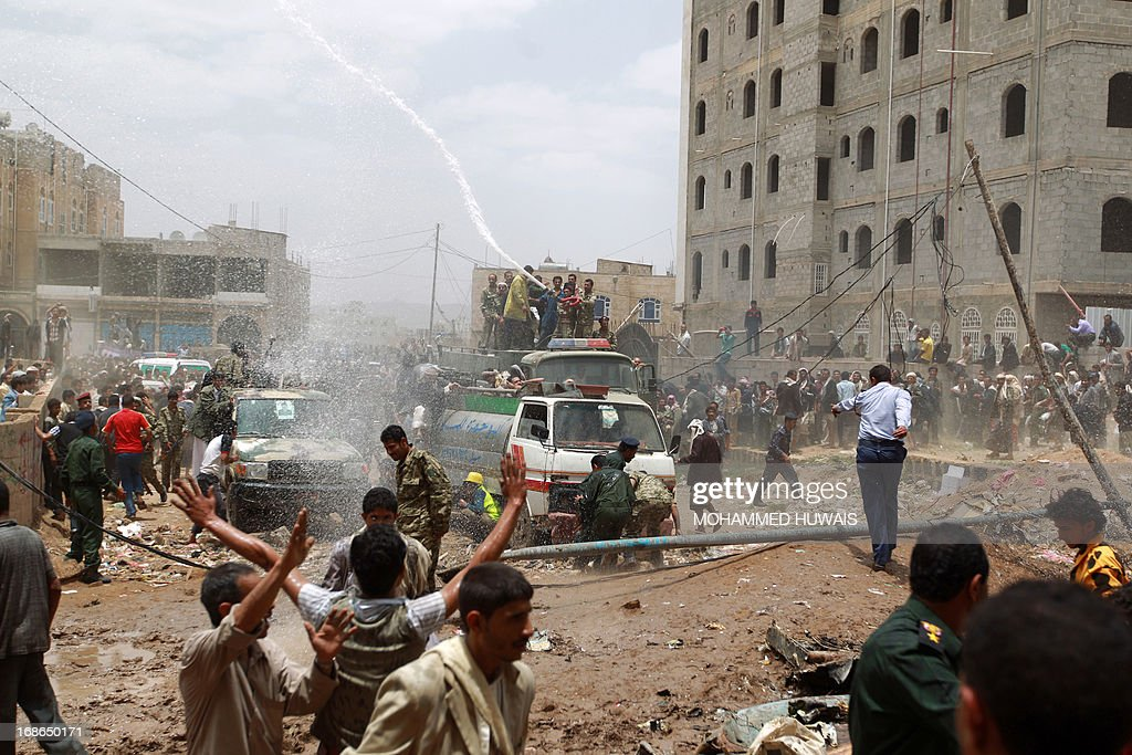 Yemeni firefighters react at the scene after a Russian-made Yemeni military jet crashed into a residential district of the capital Sanaa, on May 13, 2013, killing the pilot, officials said. Witnesses said the plane exploded in the air before crashing and debris from the aircraft scattered across the area, causing light damage to buildings and shattering windows. AFP PHOTO / MOHAMMED HUWAIS