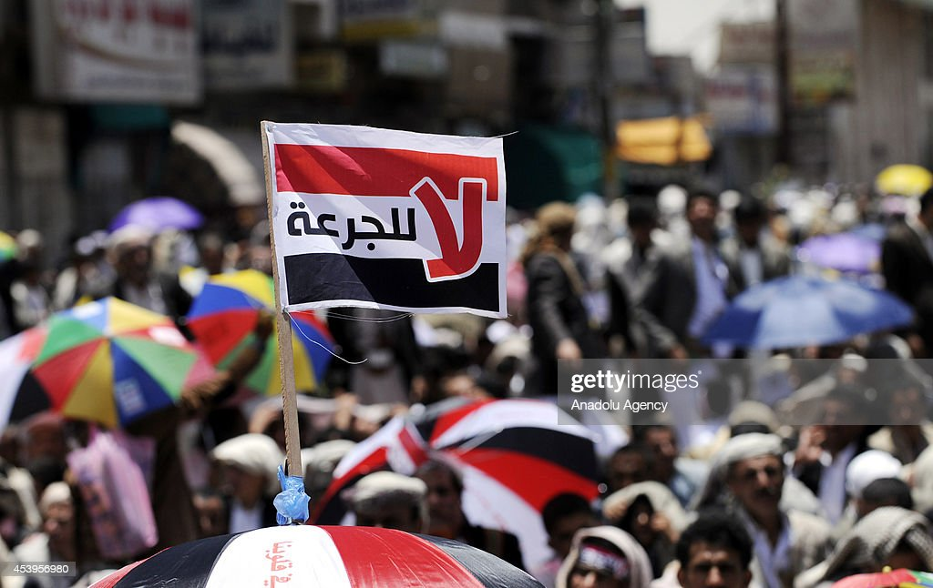 A Yemeni flag above an umbrella of protester is seen during an anti-government protest in Sanaa, Yemen on 22 August, 2014.