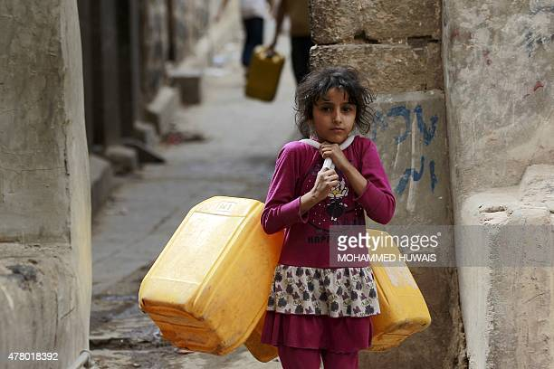 A Yemeni girl carries jerrycans to fill them with water from a public tap amid an acute shortage of water supply to houses during the fasting month...