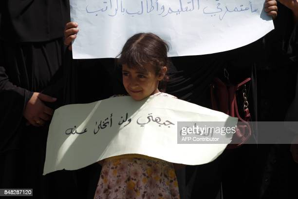 A Yemeni girl holds a placard reading 'Education is my frontline and I'm not giving it up' during a demonstration outside of the UN office demanding...