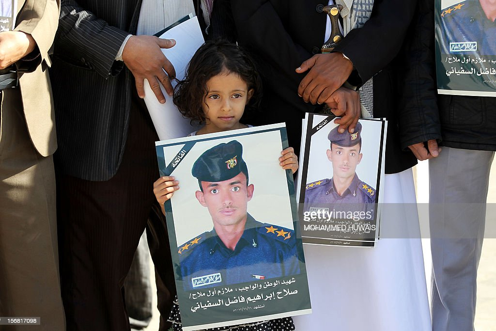 A Yemeni girl holds a portrait of a relative killed in a crash of a military plane the previous day, during a funeral service in Sanaa on November 22, 2012. The plane crashed on November 20 as it tried to make an emergency landing when an engine failed, accorading Yemen's defence ministry.